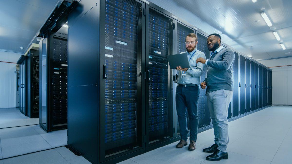 Zwei Männer stehen in Serverraum und schauen auf Laptopbildschirm