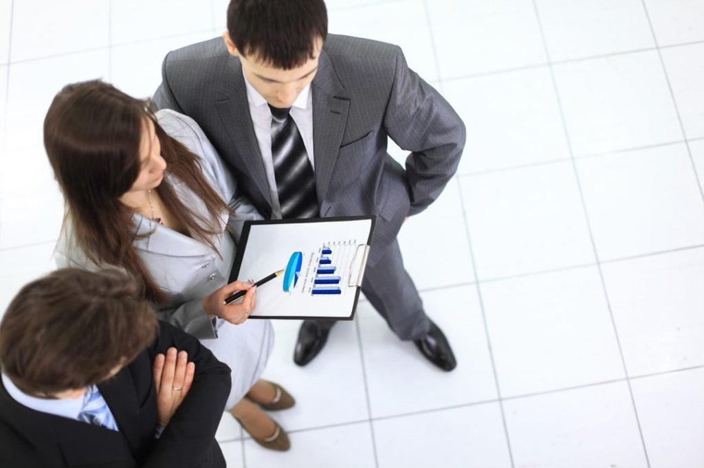 Drei Geschäftsleute blicken auf Statistik